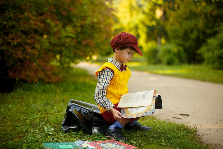 Boy in adult clothes reading